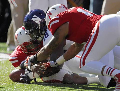 Nebraska quarterback Tommy Armstrong Jr. recovers a fumble against teammate Cethan Carter and Northwestern's Treveon Henry.