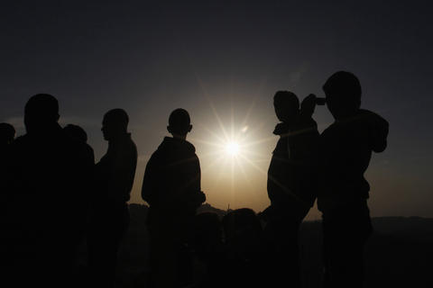 People observe a solar eclipse in Amman November 3, 2013. Sky watchers across the world are in for a treat Sunday as the final solar eclipse of 2013 takes on a rare hybrid form.