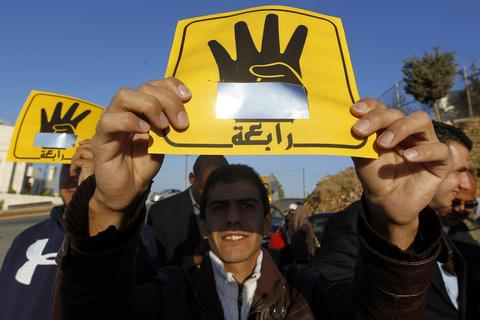 People shield their faces with specially-constructed cards showing the four-finger symbol of Rabaa, to show their support for ousted Egyptian President Mohamed Mursi, as they observe a solar eclipse in Amman November 3, 2013. Sky watchers across the world are in for a treat Sunday as the final solar eclipse of 2013 takes on a rare hybrid form.