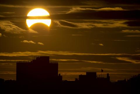 A partial Solar eclipse is seen just after sunrise over the Queens borough of New York across the East River on November 3, 2013 in New York.