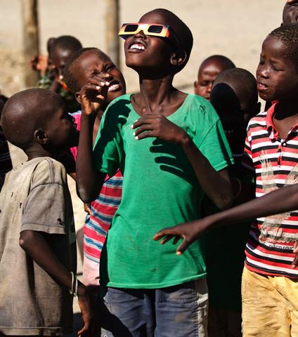 "A boy looks through a pair of special tainted glasses of the rare solar eclipse in Kalokol in Turkana on November 3, 2013.  Astronomy enthusiasts in Kenya caught a partial glimpse of a rare ""Hybrid Total Eclipse"" which hasn't been witnessed in Africa for over 40 years, though weather hampered a view of the complete eclipse."