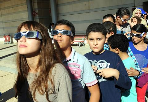 Tunisian children wear protective glasses as they watch rare solar eclipse through a cloud covering in Tunis on November 3, 2013. A rare solar eclipse swept across parts of Africa, Europe and the United States as the moon blocks the sun either fully or partially, depending on the location. The width of the shadow of the eclipse was 58 km and the maximum duration of totality, the maximum time that the moon covered the sun completely.