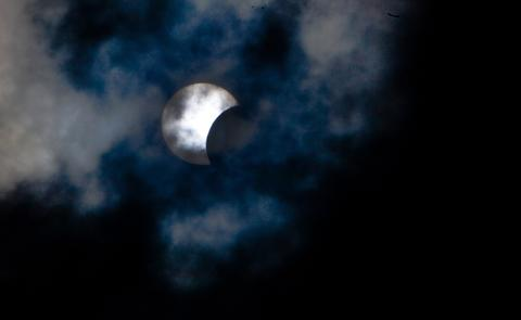 This picture taken on November 3, 2013 shows a rare hybrid solar eclipse through clouds from the Canary Island of Tenerife. A rare solar eclipse swept across parts of Africa, Europe and the United States today as the moon blocks the sun either fully or partially, depending on the location. The width of the shadow of the eclipse was 58 km and the maximum duration of totality, the maximum time that the moon covered the sun completely, was 1m 40s, on the Spanish Canary island of Tenerife.