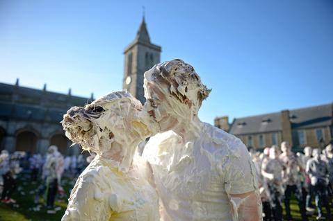 Students from St Andrew's University indulge in a tradition of covering themselves with foam to honor the 'academic family' on November 4, 2013, in St Andrews, Scotland. Every November the 'raisin weekend' which is held in the university's St Salvator's Quadrangle, is celebrated and a gift of raisins (now foam) is traditionally given by first year students to their elders as a thank you for their guidance and in exchange they receive a receipt in Latin.