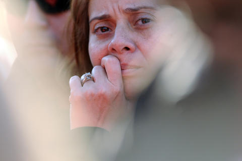 A woman in the crowd watches at the scene Monday.