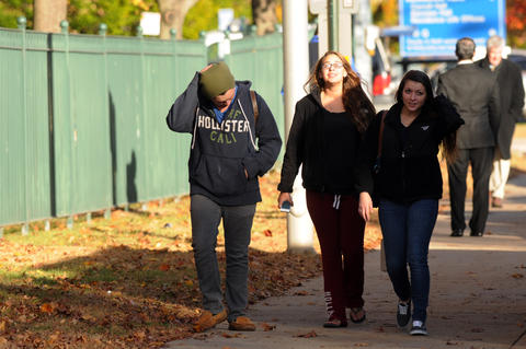 Three young people leave campus after the lockdown was lifted Monday afternoon.