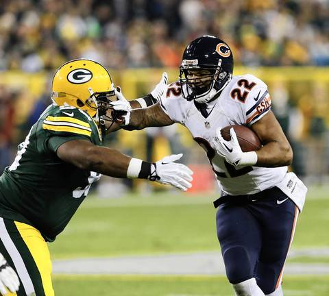 Matt Forte carries for some yardage while keeping away Packers defensive end B.J. Raji during the second quarter.