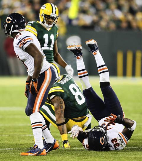 Charles Tillman falls on his back after assisting in the tackle of the Packers' Andrew Quarless.