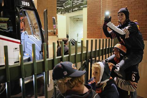 Bears fan Heather Hartman sits atop the shoulders of her cousin, Ryan Camper, as she takes photos of Chicago Bears players arriving prior to their game against the Green Bay Packers in Green Bay.