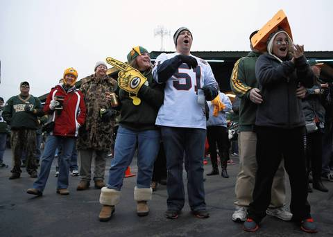 Chicago Bears fan Joe Levin (51), of Grayslake, watches a tailgating band perform while surrounded by Green Bay Packers fans outside Lambeau Field.