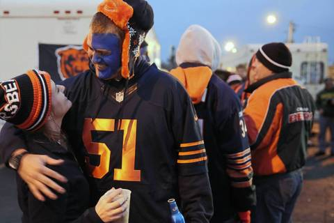Bears fan Rob Brown hugs his girlfriend Kate Parker while enjoying the tailgating festivities prior to the Green Bay Packers taking on the Chicago Bears at Lambeau Field.