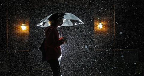 Daily Press photographer Jonathon Gruenke's strobe illuminates falling rain Thursday evening as Christopher Newport University sophomore Macy Rust walks through campus.