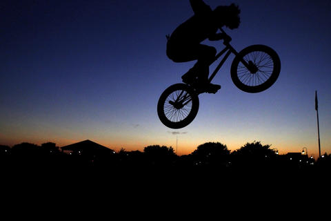 "Phillip Reed, 18, of Hampton practices bike tricks as the sun sets at Buckroe Beach Tuesday evening. ""It keeps me out of trouble,"" said Reed of biking. ""It's a cool hobby and sport. Hopefully I'll get sponsored one day."""