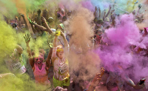 Lidia Hearing, left, and Sherie Ochoa, center, scream as crowds of people throw color bombs into the air during Sunday's Color Me Rad 5k run through Newport News. The color bombs are packets filled with colored corn starch.
