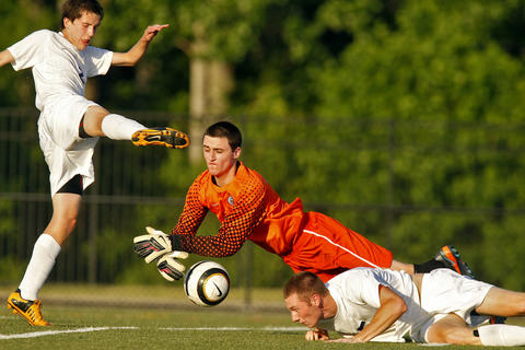 Jamestown goalie Trevor Hartnett, center, dives for the ball in between Lafayette's Jason Eckenrode, left, and David Lees during Thursday's Region I soccer tournament semifinal game.