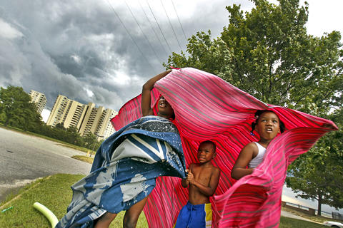 Jacquela Wynn, left, Zyion Jones, center, and Serenity Jones attempt to take cover underneath a blanket as high winds, rain and storm clouds approach Huntington Beach Thursday.
