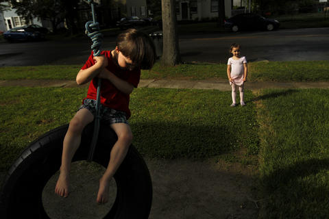Sophie Brooke, right, watches her three-year-old twin brother, Matthew Brooke, ride a tire swing in Hilton Village Wednesday afternoon.