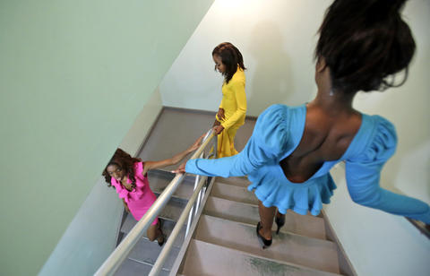 From left Hampton University students Janae Hilton, Corine Taylor, and Laquita Baker walk down a flight of stairs to take the stage during Friday evening's HU Rips the Runway: Black Reign Fashion Show.