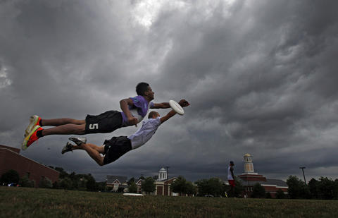 Chase Snead, 18, left, and Aaron Richards, 23, dive through the air to catch a frisbee as storm clouds approach in the distance over the campus of Christopher Newport University Tuesday evening. Snead and Richards were practicing ultimate frisbee drills with their club teammates.