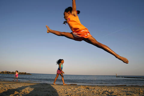 Tori McLean, 8, leaps through the air while practicing gymnastics moves with Leila Harris, 6, center, at Buckroe Beach Wednesday evening. Hundreds of people flocked to the beach as temperatures rose into the upper 80's.