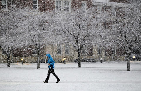 A Christopher Newport University student walks across campus through the snow Sunday evening.