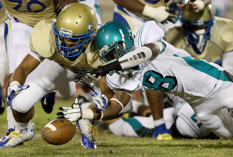 Darius Howell of Woodside and Breon Baskerville of Phoebus dive to recover a Woodside fumble during the third quarter Friday at Darling Stadium. Phoebus recoverd the ball. No Mags, No Sales, No Internet, No TV