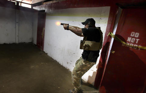 Master Instructor Brandon Wright demonstrates close quarters battle in a tac house at their Shacklefords, Virginia facility. The tac house allows the company to train with live ammunition. The company, International Training Incorporated, trains local and federal law enforcement for to deal with a variety of tactical situations.
