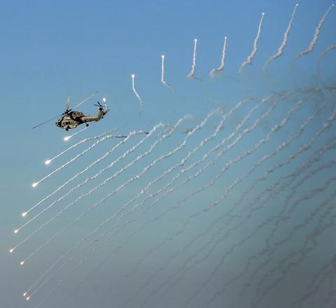 A Seahawk helicopter from the USS Eisenhower drops flares during an air power display for the civilians riding home to Norfolk Friday.
