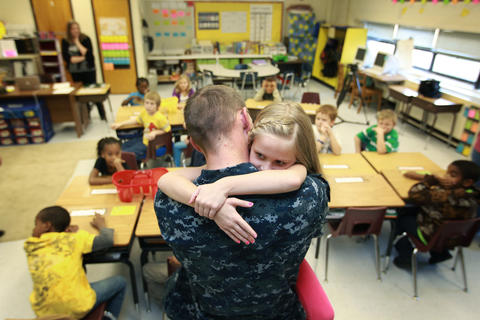 Hardy Elementary student Kendal Young hugs her father Adam Lemons after he surprised her at school Tuesday. Lemons had just arrived home from an eight month deployment on the USS Carr.