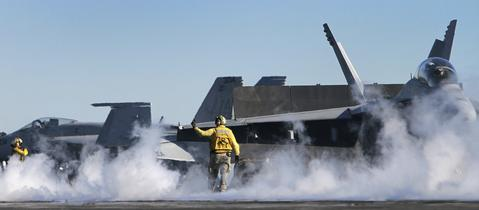 A shooter on the USS Enterprise gets the next F-18 ready Friday for launch during flight operations as the carrier makes it's way home for the last time.