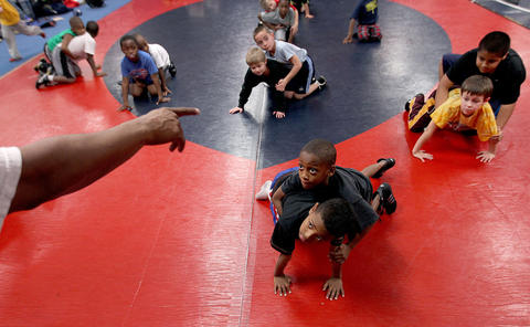 Boys and girls from ages 2 to 14 take instruction on wrestling during a training session of the Warriors Wrestling Association at Denbigh High. The group prepares children to compete in the High School ranks. No Mags, No Sales, No Internet, No TV