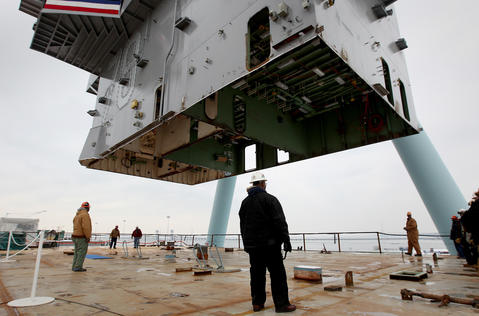 "Curtis ""Doc"" Eley (center) supervises as the island is lowered onto the deck of the carrier Gerald R. Ford Saturday at Newport News Shipbuilding."