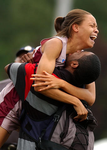 Octavia James of Heritage celebrates with her best friend Lawrence Kirby after winning the 300 meter hurdles Saturday at the State Outdoor Track and Field Championships at Todd Stadium.