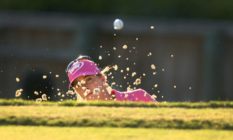 Paula Creamer hits out of the bunker during the second playoff on the 18th green against Jayai Shin Sunday at Kingsmill.