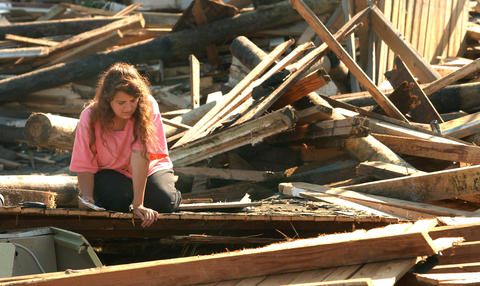 Melody Heidlebaugh searches through the rubble of her Burwell Bay home Friday evening after the storm surge created by Isabel destroyed the Bayhouse Restaurant and several homes and cottages along the James River. Many residents of the area will be moving to emergency Red Cross shelters.