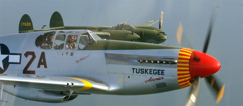 A P-51 Mustang and P-38 Lightning fly in close formation May 11, 2012, in a demonstration previewing the Langley Air Show.