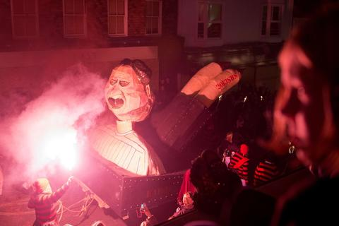 An effigy is pulled through the streets during the Bonfire Night celebrations on November 5, 2013 in Lewes, Sussex in England.Bonfire Night is related to the ancient festival of Samhain, the Celtic New Year. Processions held across the South of England culminate in Lewes on November 5, commemorating the memory of the seventeen Protestant martyrs. Thousands of people attend the parade as Bonfire Societies parade through the narrow streets until the evening comes to an end with the burning of an effigy, or 'guy,' usually representing Guy Fawkes, who died in 1605 after an unsuccessful attempt to blow up The Houses of Parliament.