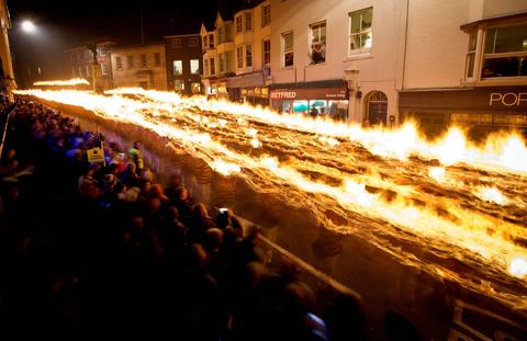 Crowds gather to watch as Bonfire societies parade through the streets during the Bonfire Night celebrations on November 5, 2013 in Lewes, Sussex in England. Bonfire Night is related to the ancient festival of Samhain, the Celtic New Year. Processions held across the South of England culminate in Lewes on November 5, commemorating the memory of the seventeen Protestant martyrs. Thousands of people attend the parade as Bonfire Societies parade through the narrow streets until the evening comes to an end with the burning of an effigy, or 'guy,' usually representing Guy Fawkes, who died in 1605 after an unsuccessful attempt to blow up The Houses of Parliament.