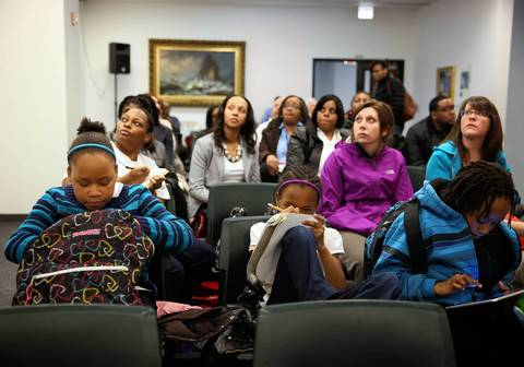 Students do their homework during a public hearing in April on the proposal to close Dumas Technology Academy and consolidate the school with Wadsworth Elementary. The hearing was held at Chicago Public Schools headquarters.
