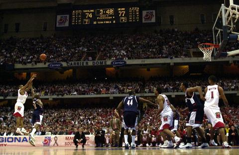 Juan Dixon releases a 3-pointer over Taliek Brown to tie the game at 77 in the second half.