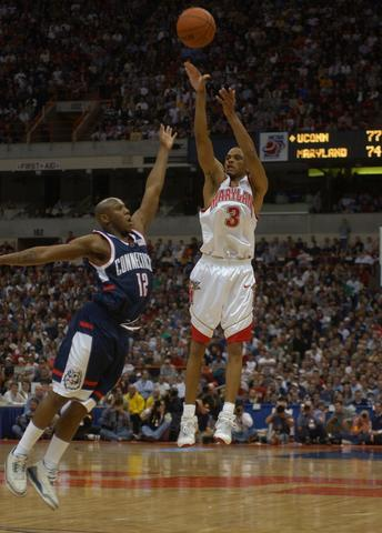 Juan Dixon releases a 3-pointer over UConn's Taliek Brown to tie the game at 77 in the second half.