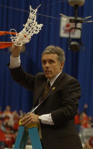 Gary Williams holds the net after it was cut down following the victory.