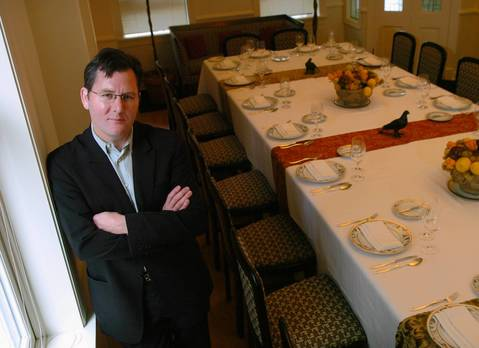Charlie Trotter poses in a dining room of his restaurant at the time he said he would no longer serve foie gras.