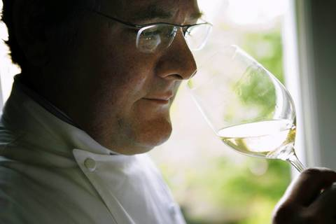 Chef Charlie Trotter smells a glass of wine at Charlie Trotter's.