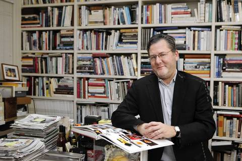 Charlie Trotter in his office above Charlie Trotter's restaurant. Trotter's walls are lined with floor to ceiling bookshelves containing cookbooks as well as biographies and books on philosophy.