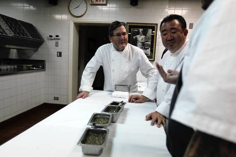 Charlie Trotter watches as guest chefs Tetsuya Wakuda and Sean Brock discuss a dish during Trotter's 25th anniversary dinner.