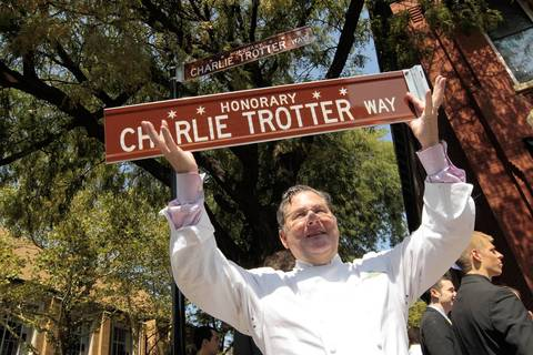 """Chef Charlie Trotter holds aloft a duplicate honorary street sign on Armitage Avenue west of Trotter's restaurant. The sign, bearing the name """"Charlie Trotter Way,"""" was unveiled during an event honoring Trotter on his last day accepting patrons at his nearby restaurant."""