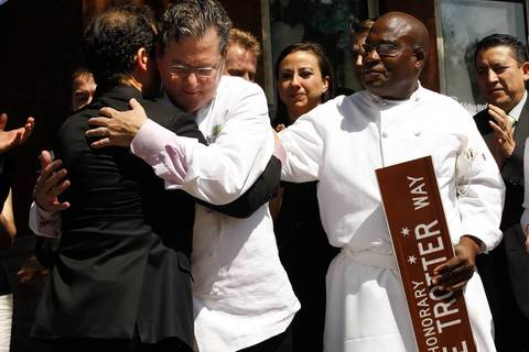 Long-time employee Ubaldo Muzariegos, left, is hugged by Chef Charlie Trotter as Chef Reginald Watkins, right, a former employee, looks on at the unveiling of an honorary street sign.