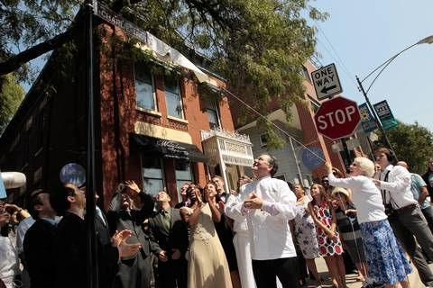 Chef Charlie Trotter, center, wearing white chef jacket, watches as his mother, Dona-Lee Trotter, right, removes the covering from an honorary street sign on Armitage Avenue west of Trotter's restaurant.