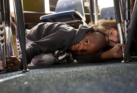 Photo Of The Week: Oct 12-Oct 18, 2013   Jaiden Pollard and Samya Meisel huddle together under desks as students in Mandy Mize's second-grade class participate in the Great SouthEast ShakeOut earthquake drill at Alfred S. Forrest Elementary School in Hampton on Thursday.